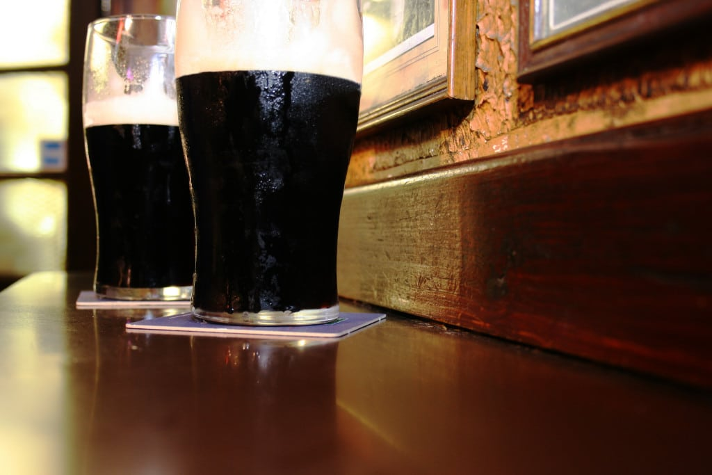 Two glasses of famous black Irish stout in Irish pub on wooden bar ** Note: Shallow depth of field