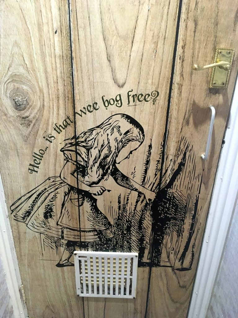 The door of the restroom at this Belfast cafe features an illustration from Alice in Wonderland
